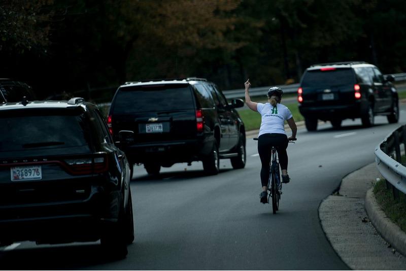 Женщина показывает неприличный жест кортежу Дональда Трампа