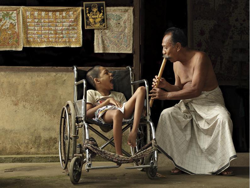 Мужчина играет на бамбуковой дудочке чтобы развеселить мальчика, прикованного к инвалидной коляске.