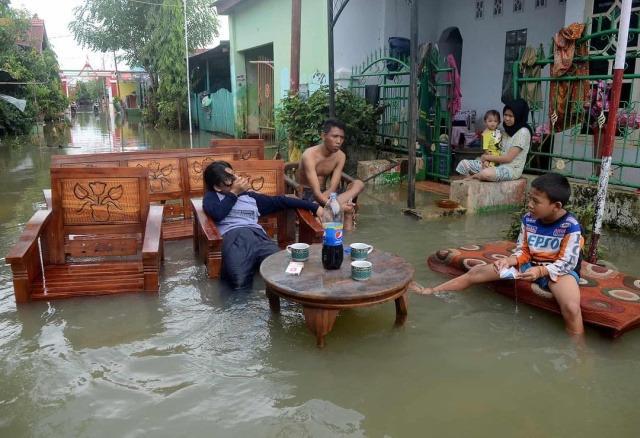 Жители Макассара сидят возле своих домов после наводнения. Южный Сулавеси, Индонезия