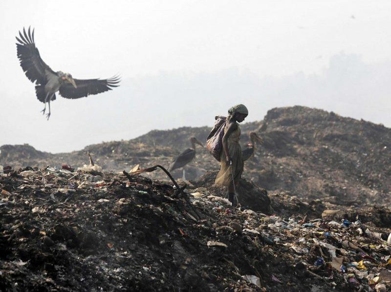 Женщина на свалке мусора на окраине города Гувахати.