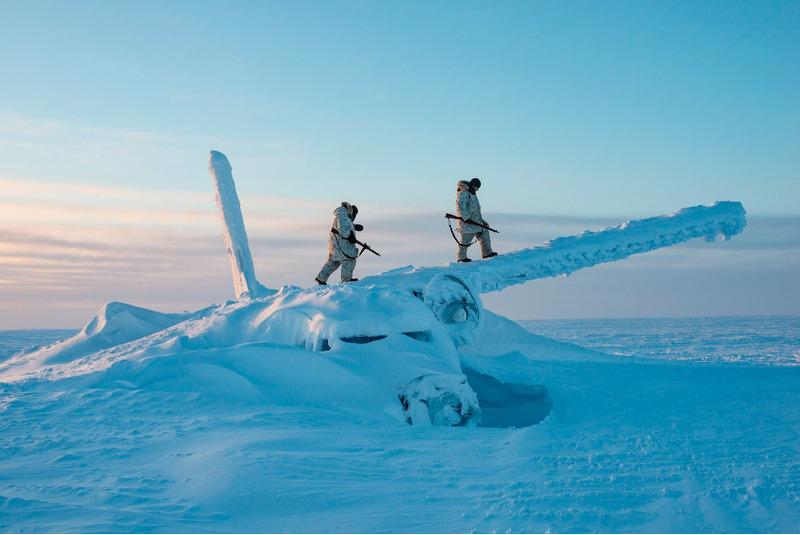 Канадские солдаты взбираются на обломки самолета, примерно в тысяче миль к югу от Северного полюс.