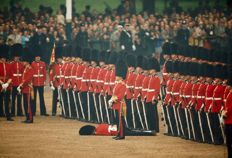 Ирландская гвардия продолжает стоять по стойке смирно, хотя один из них потерял сознание. Лондон, июнь 1966