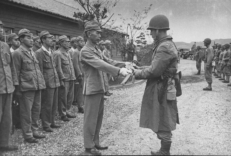 Капитуляция японской военно-морской базы Курихара, расположенной на острове Хонсю. Японец протягивает меч американцу с диким нарушением этики меча - рукоятью под правую руку и острым лезвием вперёд. С точки зрения японца - он наносит американцу тяжелейшее оскорбление. 1945 год.