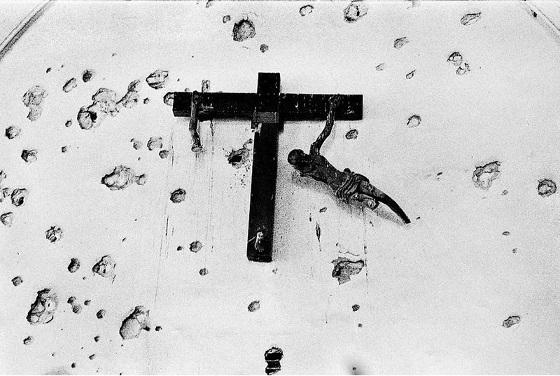 Поврежденное распятие, висящее на изрешеченной пулями стене. Суэц, Египет, 1973 год.