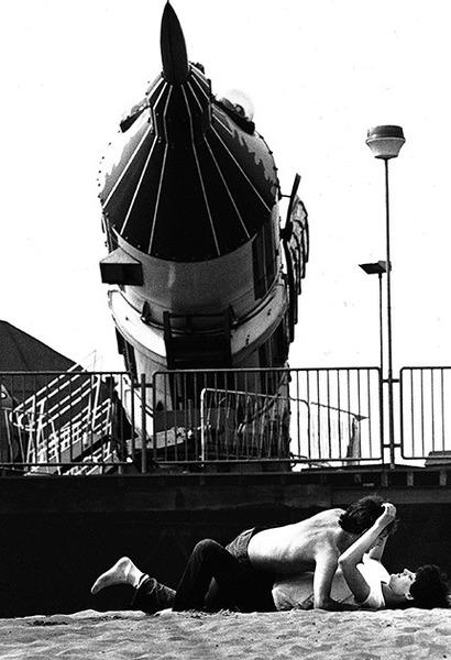 Молодая парочка резвится на песке близ ракеты. Англия, 1982 год.