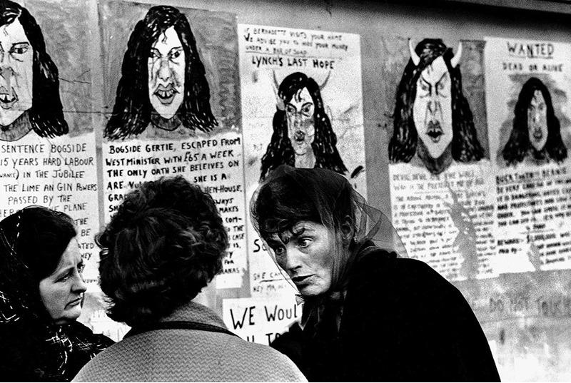 Три женщины на фоне серии постеров, критикующих республиканскую активистку Бернадетт Девлин Макалиски после ее избрания в Вестминстерский дворец. Северная Ирландия, 1969 год.