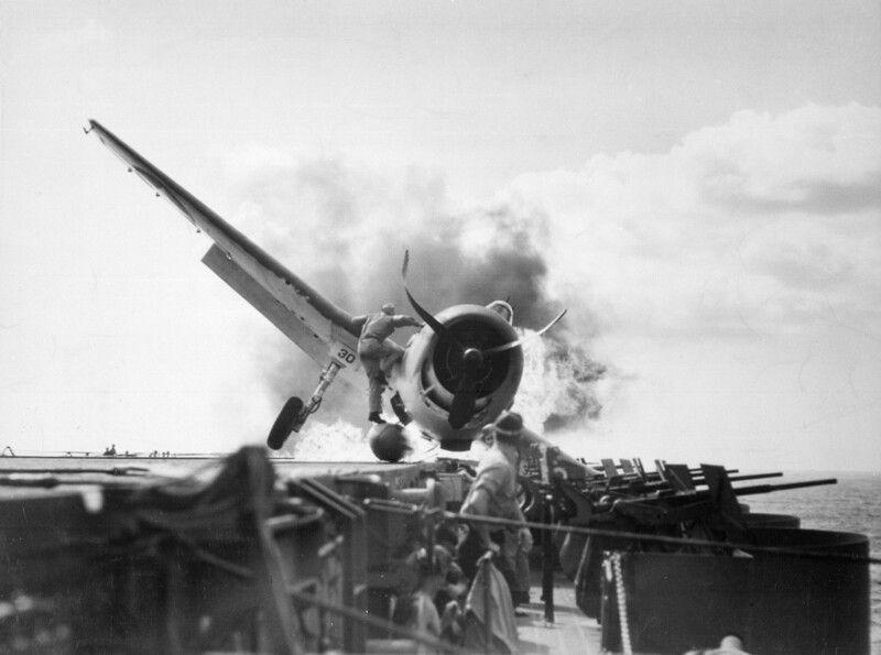 Подбитый Grumman F6F Hellcat неудачно сел на авианосец USS Enterprise. И офицер корабля запрыгивает в огонь чтобы вытащить раненого летчика. Оба выживут.