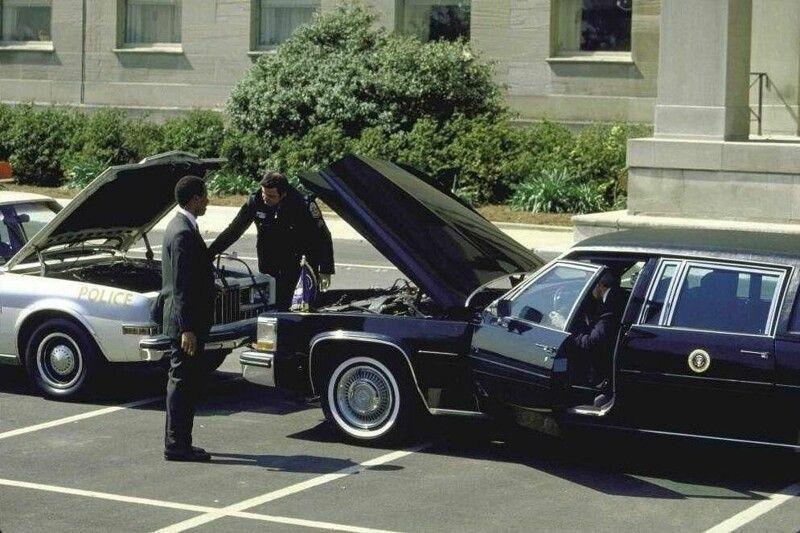 Полицейский прикуривает свой патрульный автомобиль от лимузина президента США Рональда Рейгана, 1984 год